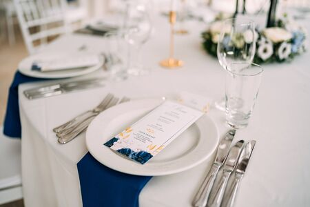 Wedding dinner table reception. White plate on the table, three forks on left, three knives on the right. The wedding menu is in the plate. Top view