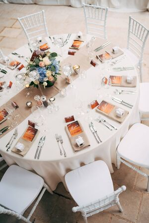 Wedding dinner table reception. Round table with white tablecloth with brown runner on table. Vienna nested in brown napkins, a bouquet of flowers is on the table. White Chiavari chairs with pillows.