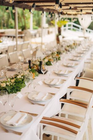 A long table with a white tablecloth, a garland with incandescent light bulbs over it. Wooden white chairs. Flower composition in the center of the table