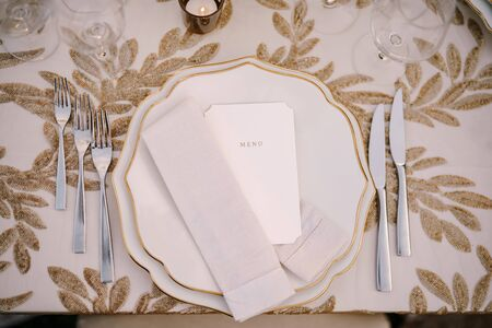 Wedding dinner table reception. Delicate creamy pastel tones of tablecloths and plates on table, three forks left and two knives on right, glasses and candles in candlesticks