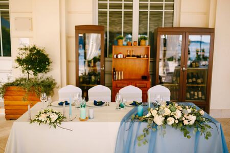 White rectangular table of newlyweds with four chairs, white-blue tablecloth, floral arrangements with eucalyptus leaves and candles, against the background of wine cabinets