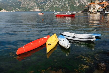 Six kayaks moored near the shore in the city of Perast, Montenegro. Kayak red, yellow, white-blue