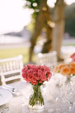 Wedding dinner table reception. A bouquet of small peony pink roses in a transparent glass vase on a table in the sun, with the backs of Chiawari chairs in the background