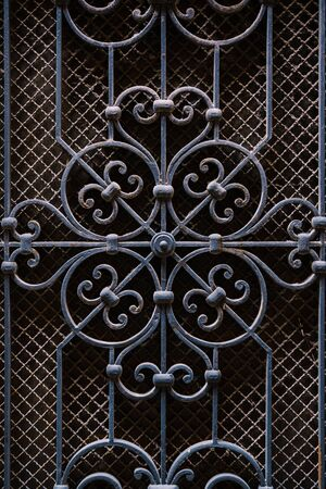 Metal forging on door, blue, against the background of small mesh of slave. Elements of architectural decoration of ancient buildings - old metal forged door. Forged gates, vintage style