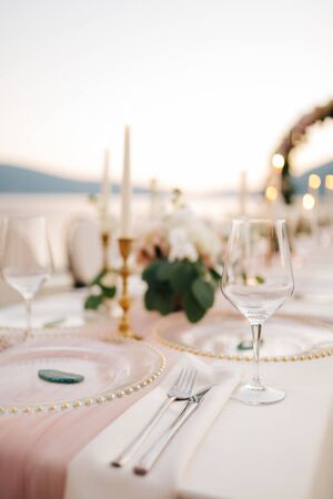 Close-up of wedding dinner table. Beautiful glassware - plates with golden beads, wine glasses, knives and forks, on background of candles and flower arrangements. Wedding outside, sunset background