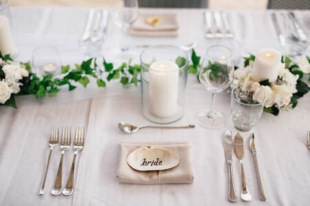 Close-up of a wedding dinner table. The inscription BRIDE on the shell in center of the table. Serving a table - knives, forks, glasses, wine glasses, candles, against background of gray tablecloth