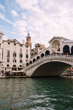 The beautiful Ponte di Rialto Bridge over Central Grand Canal in Venice, Italy, with shops, beautiful views and lots of people. Near boat station of the same name, the street leads to San Marco