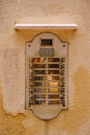 Close-ups of building facades in Venice, Italy. An old vintage intercom and a mailbox on stone wall. On door where placed this old rusty doorbells.