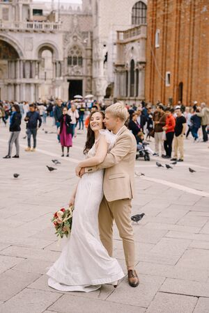 Wedding in Venice, Italy. The bride and groom are hugging in Piazza San Marco, overlooking Campanila and St. Mark Cathedral, among a crowd of tourists.