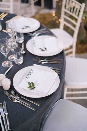 White round plates on a round table with gray tablecloth, white Chiavari chairs with white pillows. A floral arrangement in the center of the table.