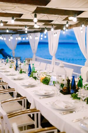 A long table, against the sea, with a white tablecloth, a garland with incandescent light bulbs over it. Wooden white chairs. Flower composition in the center of the table