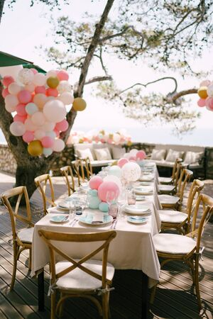 Wedding dinner table reception. A rectangular table in the style of rustic with a cream tablecloth and handmade wooden chairs. A table in the shade of trees, outside, decorated with lots of balloons