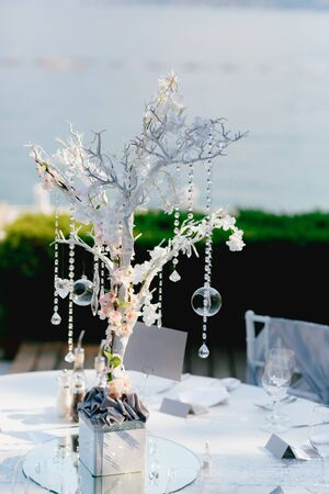 Wedding dinner table reception. Wedding table decoration - white branch from a tree, crystal pendants, candles in glass spheres, on a white table with a mirror, against the sea 스톡 콘텐츠