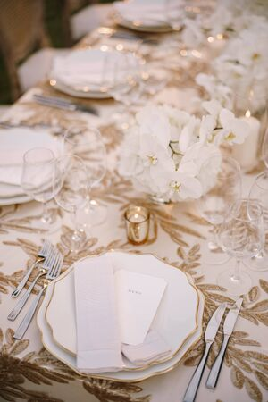 Wedding dinner table reception. Delicate creamy pastel tones of tablecloths and plates on table, three forks left and two knives on right, glasses and candles in candlesticks Stok Fotoğraf