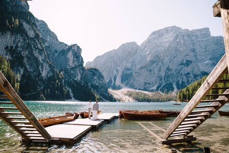 The bride and groom walk along a wooden boat dock at the Lago di Braies in Italy. Wedding in Europe, on Braies lake. Newlyweds walk, kiss, hug on a background of rocky mountains. Imagens