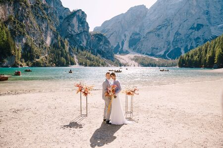 The groom puts on a ring to the bride, at the venue for ceremony, with an arch of autumn flower columns, against the backdrop of Lago di Braies in Italy. Destination wedding in Europe, on Braies lake Imagens