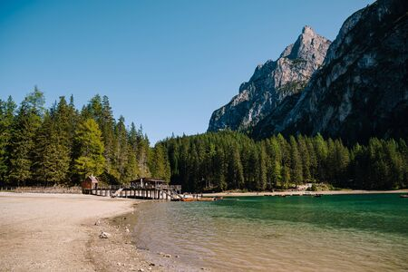 Wooden boat dock hut on the Lago di Braies on the background of rocky mountains and forests. Braies lake in the Dolomites in South Tyrol, Italy, a municipality of Braies, in the Prague Valley.