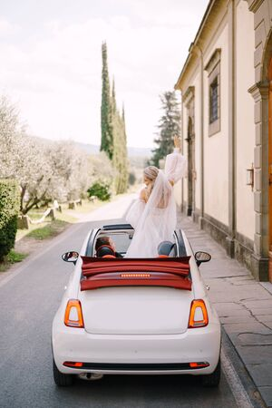 Wedding in Florence, Italy, in an old villa-winery. Wedding couple in a convertible. The bride dances on the seat, the groom behind the wheel of the car
