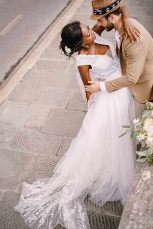 Interracial wedding couple. Wedding in Florence, Italy. African-American brid in white dress and Caucasian groom. Standard-Bild