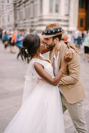African-American bride and Caucasian groom kissing among the crowd in Piazza del Duomo. Wedding in Florence, Italy. Mixed-race wedding couple Standard-Bild