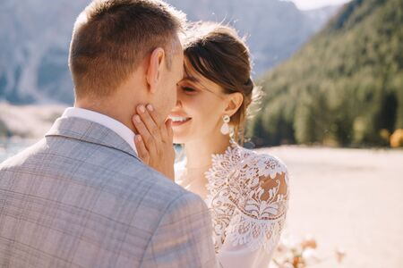 Newlyweds kiss on the spot for the ceremony, with an arch of autumn flower columns, against the backdrop of Lago di Braies in Italy. Destination wedding in Europe, at Braies lake. Imagens - 147582058