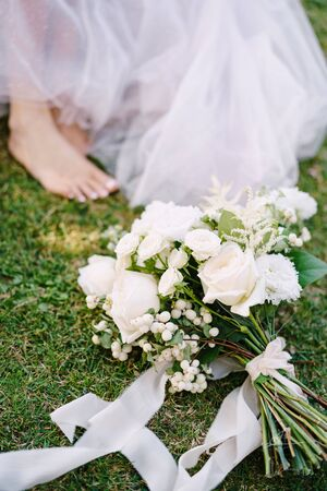 Wedding in Florence, Italy, in an old villa-winery. The white bouquet of the bride lies on the grass, barefoot legs of the bride. Standard-Bild
