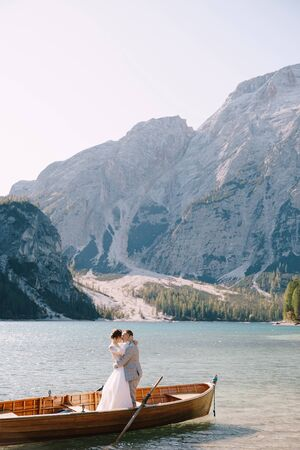 Bride and groom sailing in wooden boat, with oars at Lago di Braies lake in Italy. Wedding in Europe - Newlyweds are standing embracing in boat Imagens
