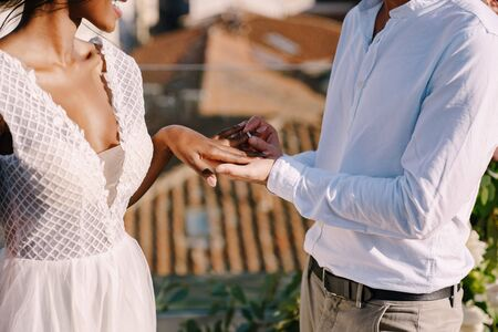 Interracial wedding couple - African-American bride and Caucasian groom. Groom puts a ring on brides finger. Destination fine-art wedding in Florence, Italy. Wedding ceremony on the roof of building