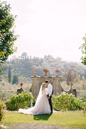 Wedding at an old winery villa in Tuscany, Italy. Round wedding arch decorated with white flowers and greenery in front of an ancient Italian architecture. The bride and groom walk in the park.