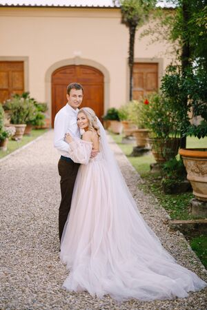 A young couple is hugging and looking at the camera. Wedding in Florence, Italy, in an old villa-winery. Standard-Bild