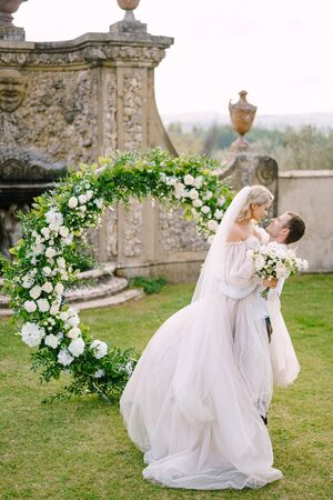 Wedding at an old winery villa in Tuscany, Italy. The groom circles the bride in his arms. Round wedding arch decorated with white flowers and greenery in front of an ancient Italian architecture.