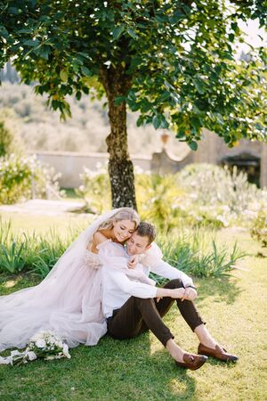 Wedding in Florence, Italy, in an old villa-winery. A wedding couple is sitting on the grass in the garden under a tree, the bride is hugging the groom.