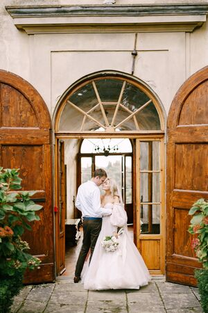 Wedding at an old winery villa in Tuscany, Italy. A wedding couple is standing near the old wooden doors in the villa-winery. Standard-Bild