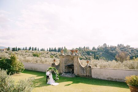 Wedding at an old winery villa in Tuscany, Italy. Wedding couple under a round arch of flowers. The groom reads wedding vows.