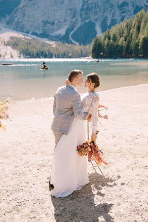 The newlyweds kiss on the spot for the ceremony, with an arch of autumn flower columns, against the backdrop of the Lago di Braies in Italy. Destination wedding in Europe, on Braies lake. Imagens