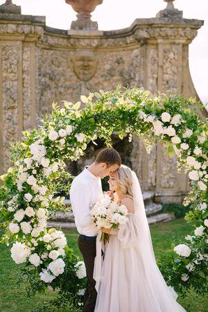 Wedding at an old winery villa in Tuscany, Italy. Wedding couple near round wedding arch decorated with white flowers and greenery in front of an ancient Italian architecture.