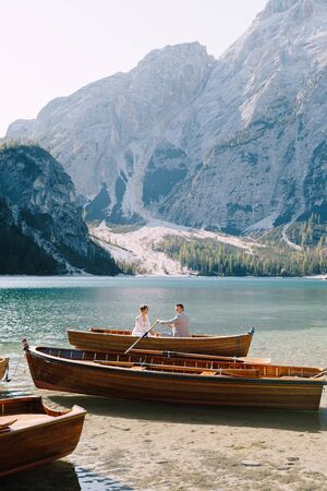 Newlyweds sail in a wooden boat on the Lago di Braies in Italy. Wedding in Europe, on Braies lake. Wedding couple - The groom rows with wooden oars, the bride sits opposite. Imagens