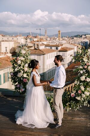 Destination fine-art wedding in Florence, Italy. A wedding ceremony on the roof of the building, with cityscape views of the city and the Cathedral of Santa Maria Del Fiore. Multiracial wedding couple