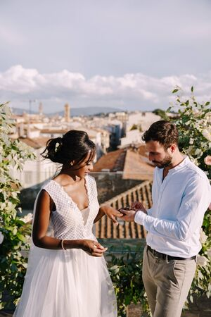 Destination fine-art wedding in Florence, Italy. A wedding ceremony on the roof of the building, with cityscape views of the city and the Cathedral of Santa Maria Del Fiore. Mixed-race wedding couple