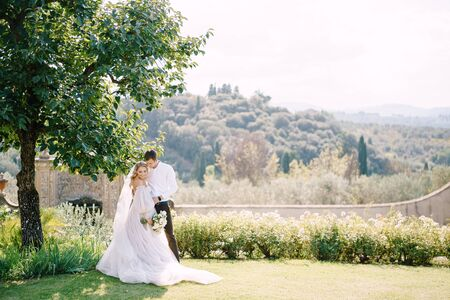 Wedding in Florence, Italy, in an old villa-winery. Bride and groom in the shade of a tree. Wedding couple walks in the garden. Standard-Bild
