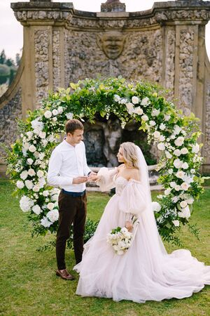 The groom puts the ring on the brides finger. Wedding at an old winery villa in Tuscany, Italy. Round wedding arch decorated with white flowers and greenery in front of an ancient Italian architecture Standard-Bild