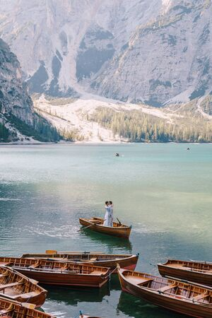 Bride and groom sailing in wooden boat, with oars at Lago di Braies lake in Italy. Wedding in Europe - Newlyweds are standing embracing in a boat.
