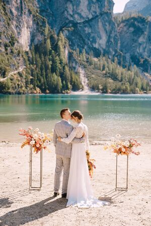 The bride and groom stand in place for the ceremony, with an arch of autumn flower columns, against the backdrop of the Lago di Braies in Italy. Destination wedding in Europe, on Braies lake.
