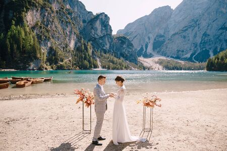 The bride puts a ring on to the groom at venue for the ceremony, with an arch of autumn flower columns, against backdrop of the Lago di Braies in Italy. Destination wedding in Europe, on Braies lake.
