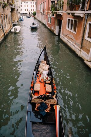 Italy wedding in Venice. A gondolier rolls a bride and groom in a classic wooden gondola along a narrow Venetian canal. Newlyweds are sitting in a boat on the background of ancient buildings.