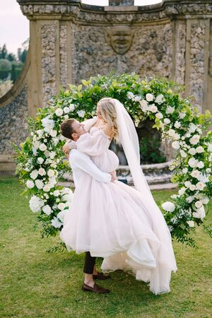 Wedding at an old winery villa in Tuscany, Italy. The groom circles the bride in his arms. Round wedding arch decorated with white flowers and greenery in front of an ancient Italian architecture. 写真素材 - 147588057