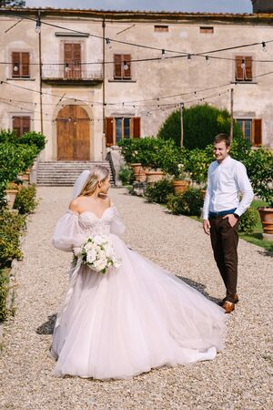 Wedding in Florence, Italy, in an old villa-winery. Wedding couple walks in the garden. Loving bride and groom. 写真素材 - 147589311
