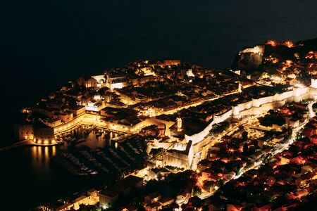 Aerial top night view on the old city of Dubrovnik, from the observation deck on the mountain above the city. Film location. The view of the city is based on the Royal Harbor.