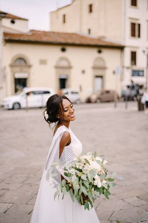 Wedding in Florence, Italy. African-American bride in a white dress and a long veil. With a magnificent bouquet of the bride in her arms.