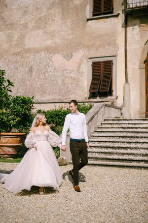 Wedding in Florence, Italy, in an old villa-winery. Wedding couple walks in the garden. Loving bride and groom.